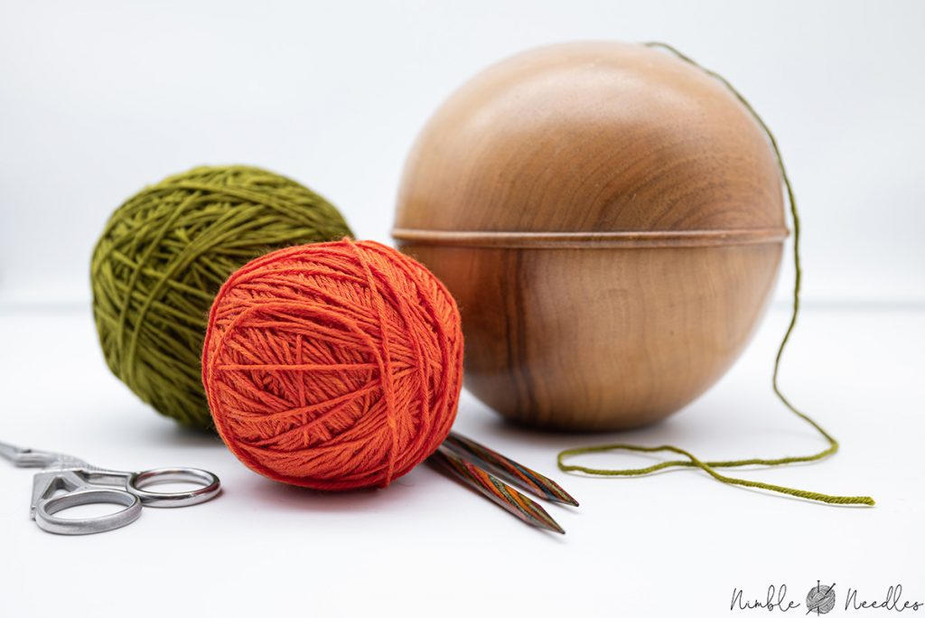 A yarn holder with 2 balls of yarns and some knitting needles in front of it