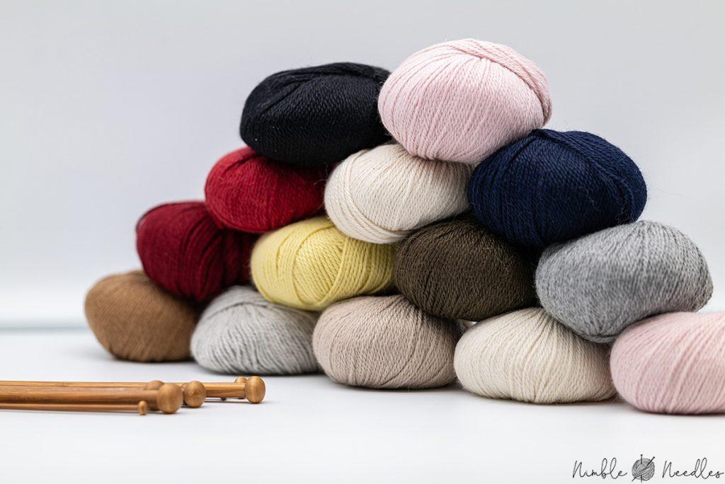 A stack of baby alpaka yarn balls with knitting needles