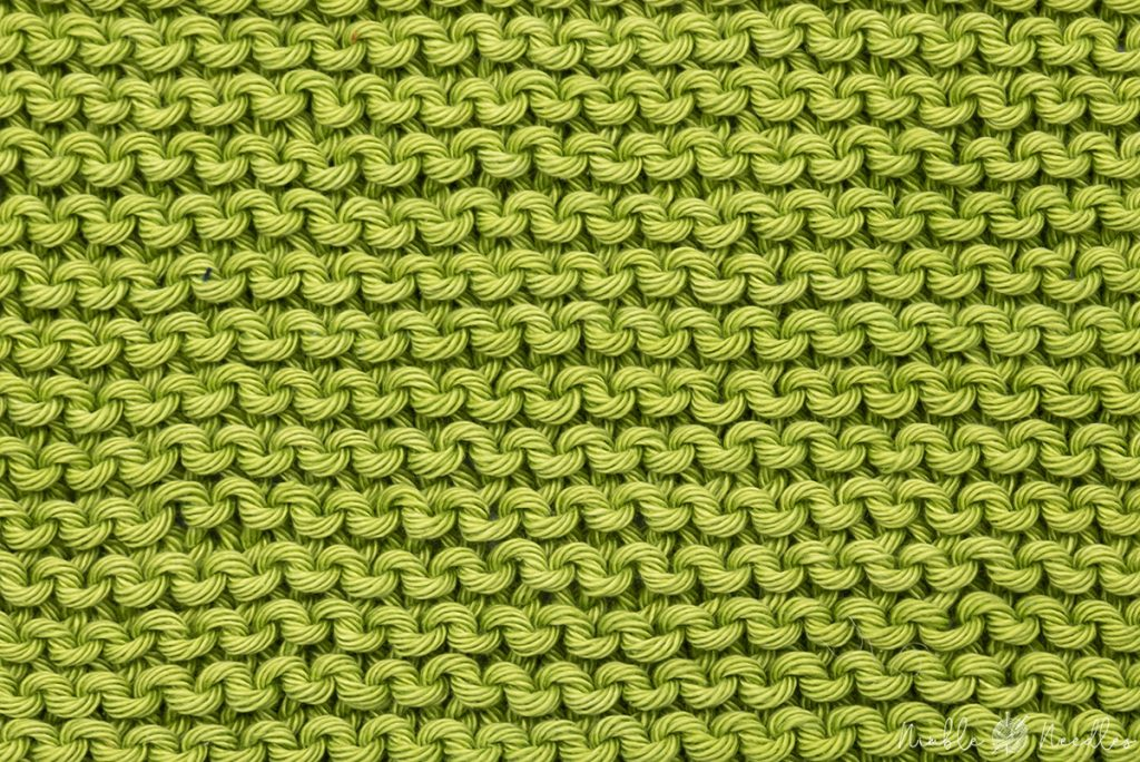 a garter stitch pattern in green cotton yarn