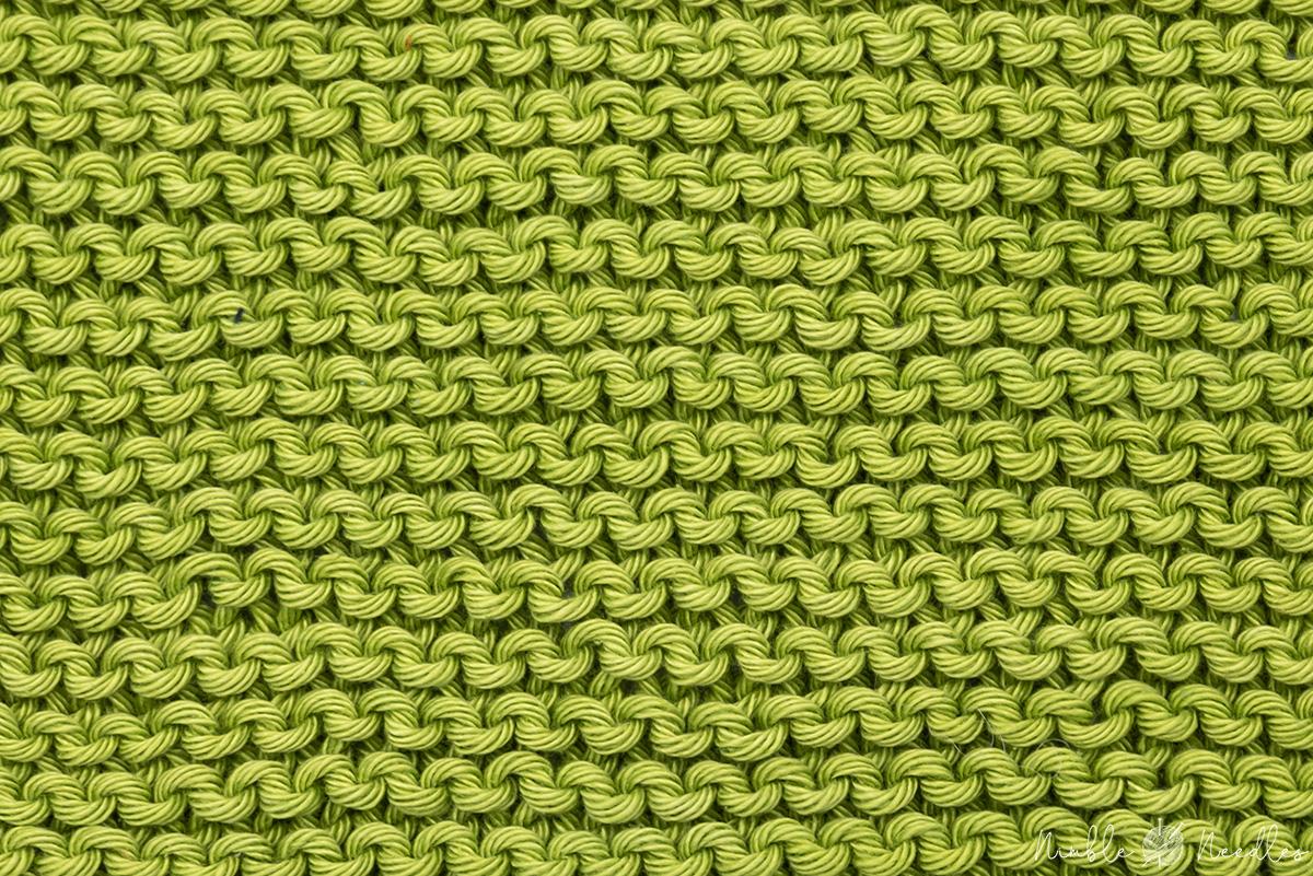 a garter stitch pattern in green cotton yarn