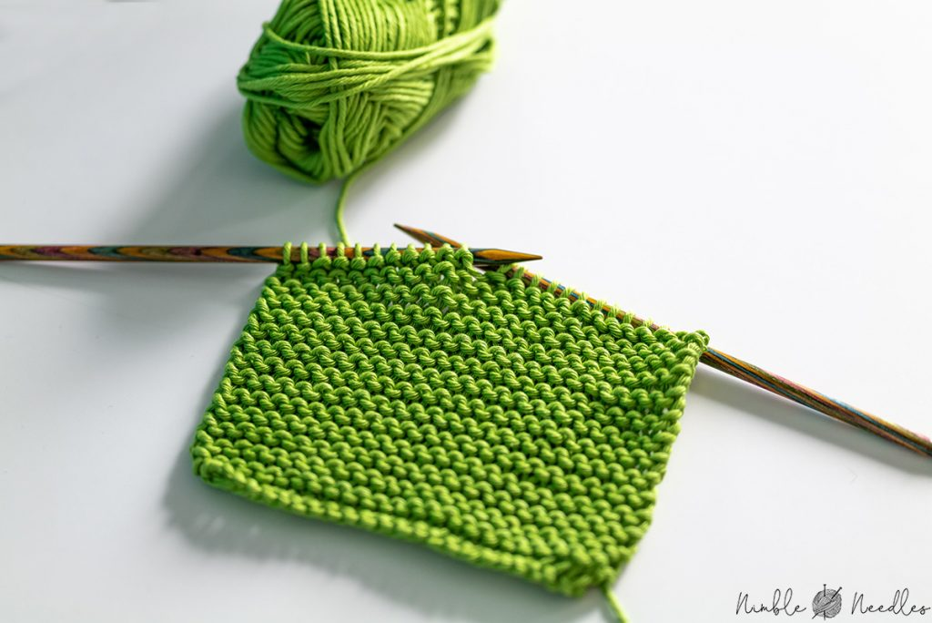 A sample swatch knitted in garter stitch on the needles