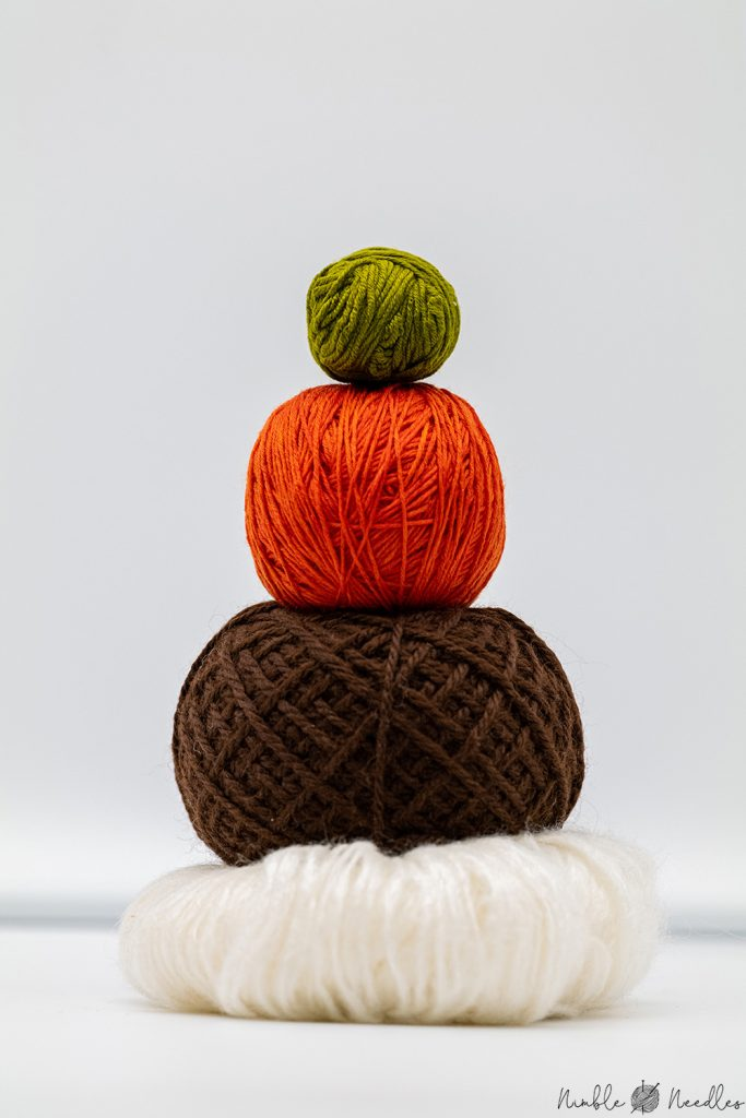 A tower with three balls of yarn stacked on top of each other