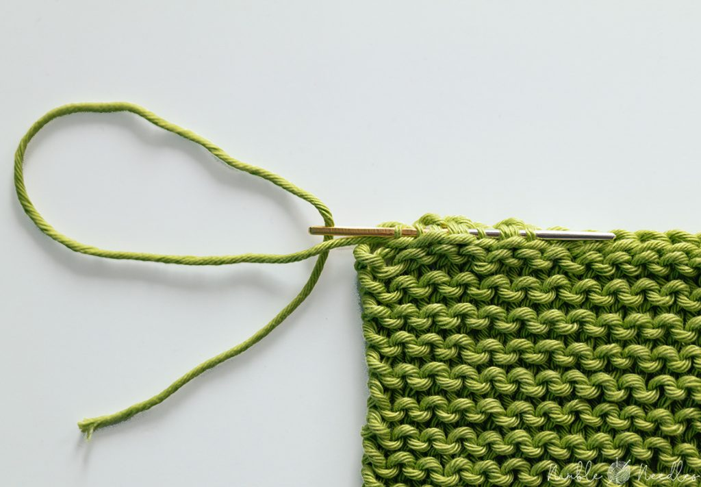 Using a tapestry needle to sew the tail of a knitting edge