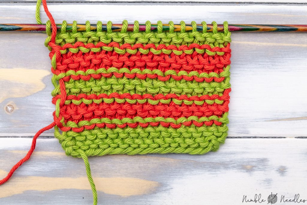 the wrong side of a swatch knit in garter stitch with stripes with floats clearly visible