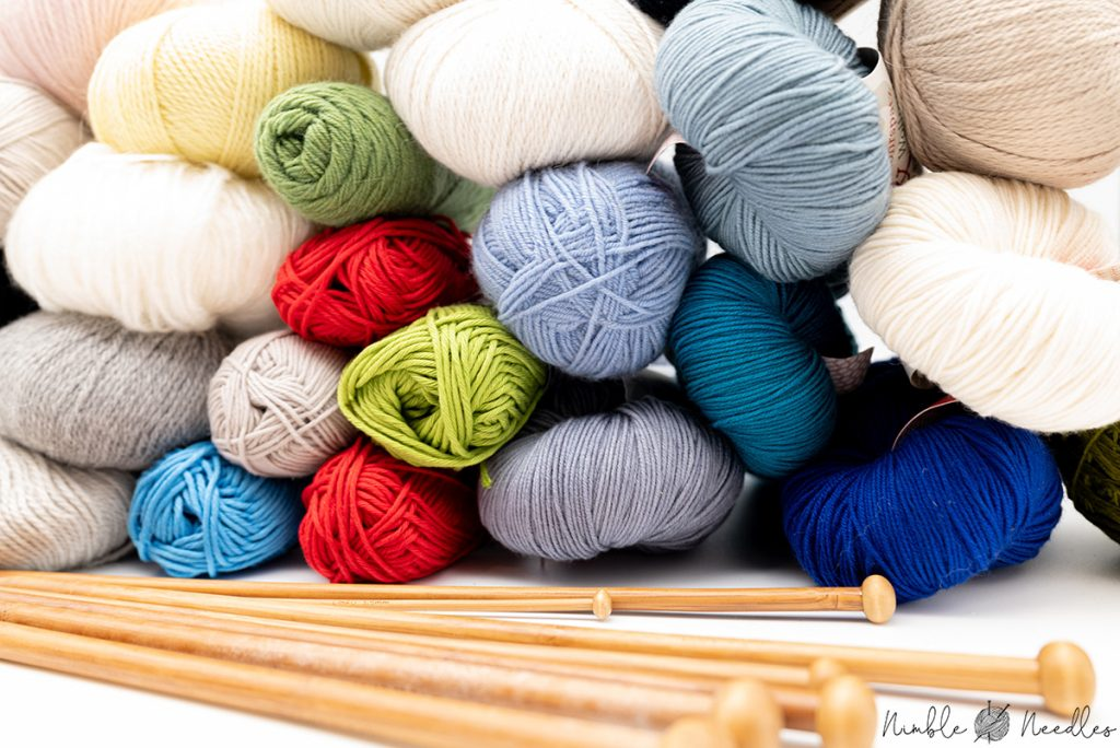 A stack of different yarns in different materials, colors, and weights