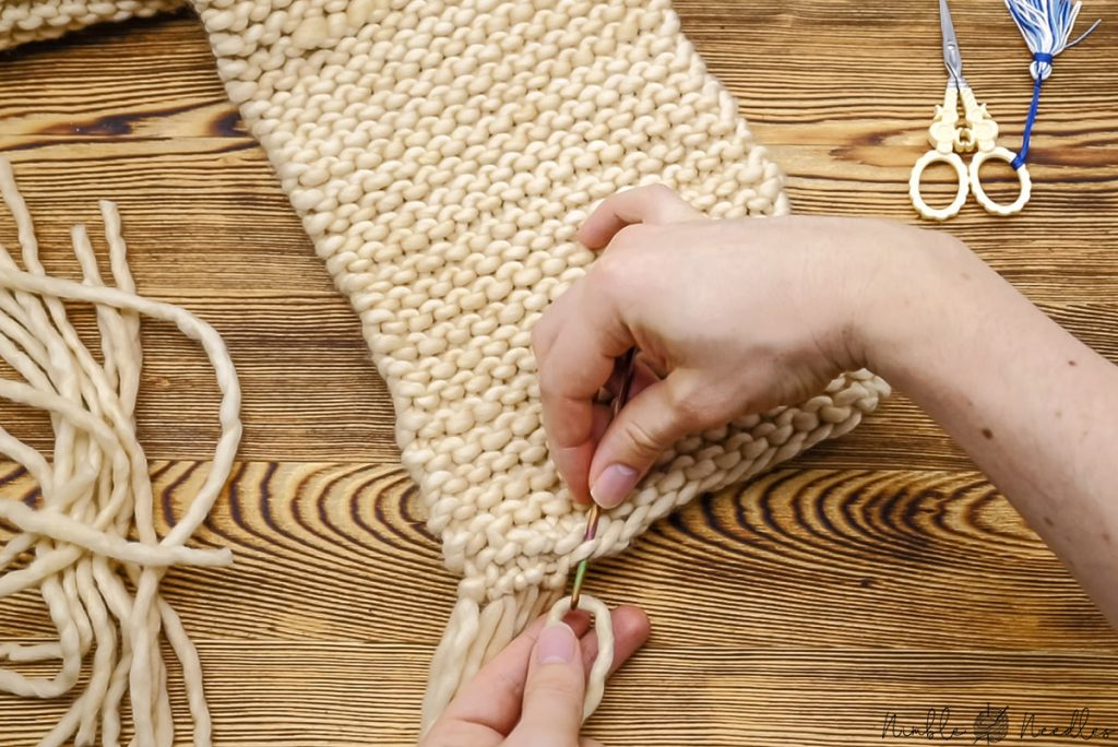 adding fringes to a scarf with a crochet hook