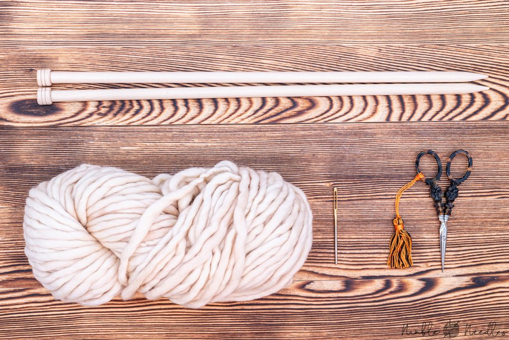 The materials you will need to knit a scarf for beginners: yarn, needles, tapestry needle and scissors