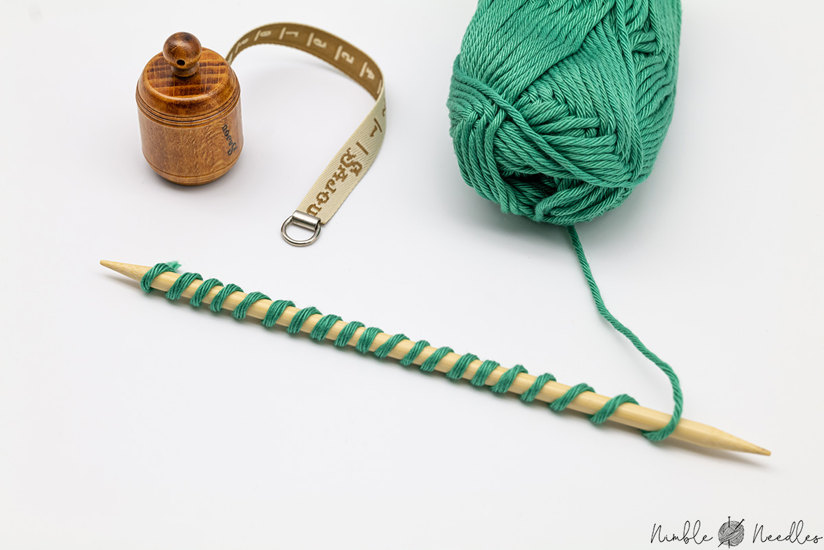 Wrapping the yarn around the needle to see how much yarn to use for a long tail cast on