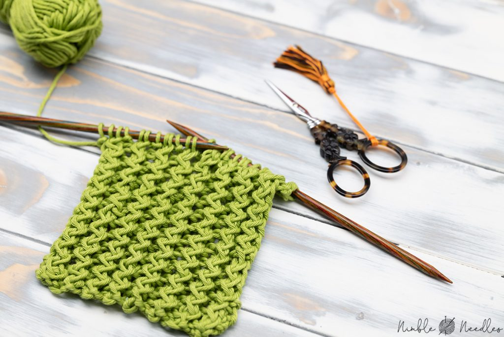 A swatch on the needles knitted in the zigzag rib stitch pattern