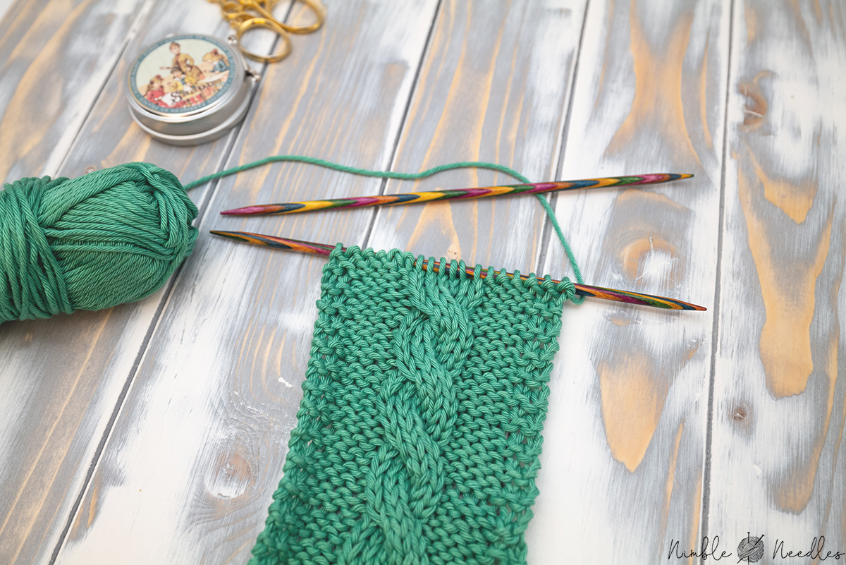 knitting on a swatch with a 3x3 cable stitch