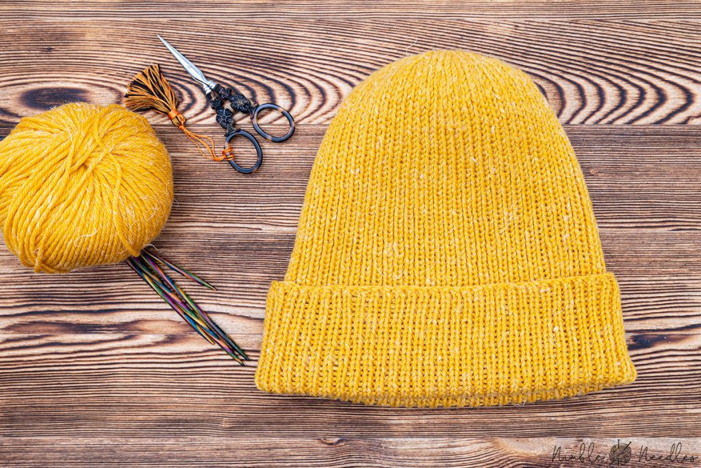 the finished men's beanie in yellow yarn
