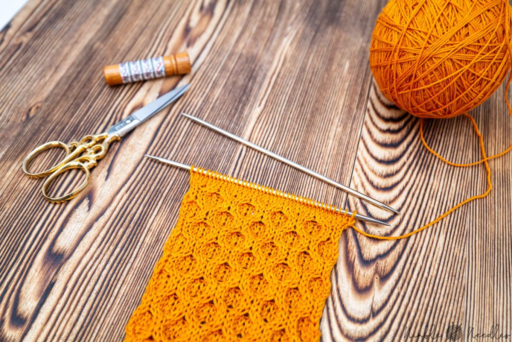 A close-up of a swatch knitting with the honeycomb cable stitch in bright orange wool