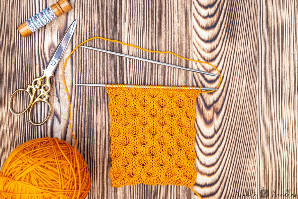 A swatch knitted with the honeycomb cable stitch in orange wool