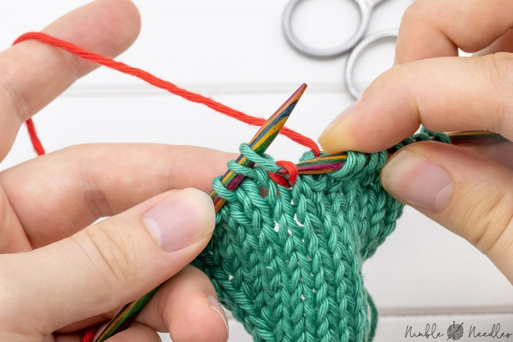 insert the left needle into the stitch one row below from behind