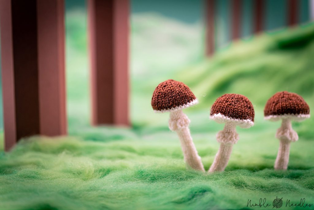 three knitted mushrooms lined up on a fake meadow made of wool rovings