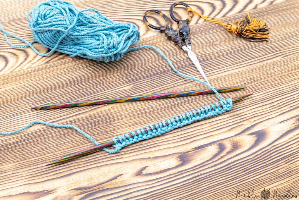 a knitted cast on on the needles with another knitting needle, blue yarn and scissors in the background