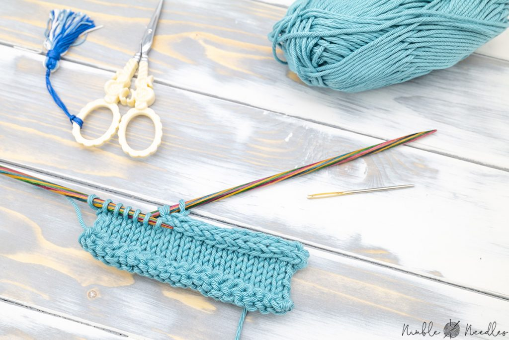 a swatch with a partially knitted icord bind off on the needles