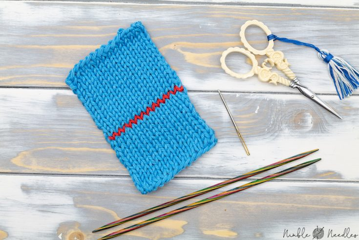 A swatch where two knitted pieces where grafted together with a kitchener stitch in a contrasting red yarn