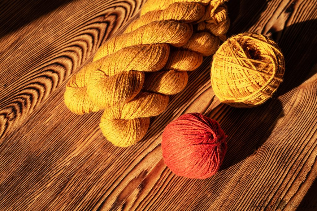 three hanks of yarn and a ball and a yarn cake next to it