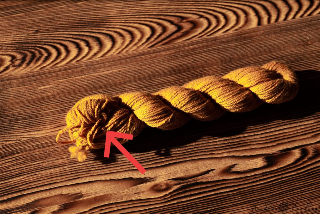 a hank of yarn and an arrow marking the spot where you need to unravel it