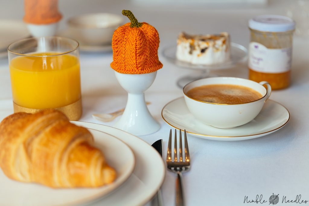 enjoying breakfast with a knitted pumpkin egg cozy as the center piece