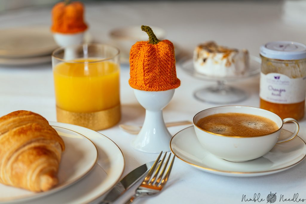 a set table with a knitted pumpkin egg cozy in the middle