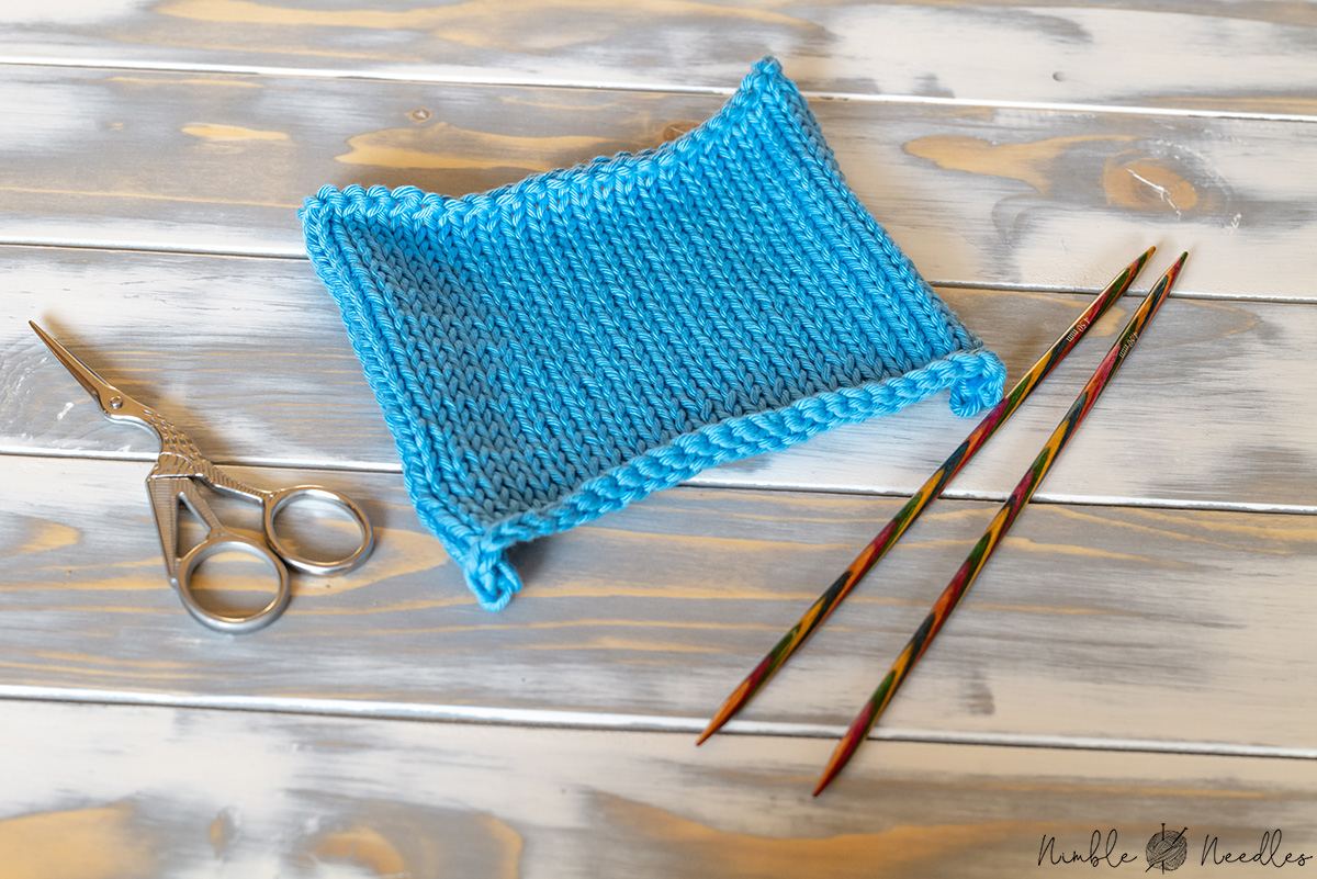 a swatch in stockinette stitch curling at the edges and at the bottom
