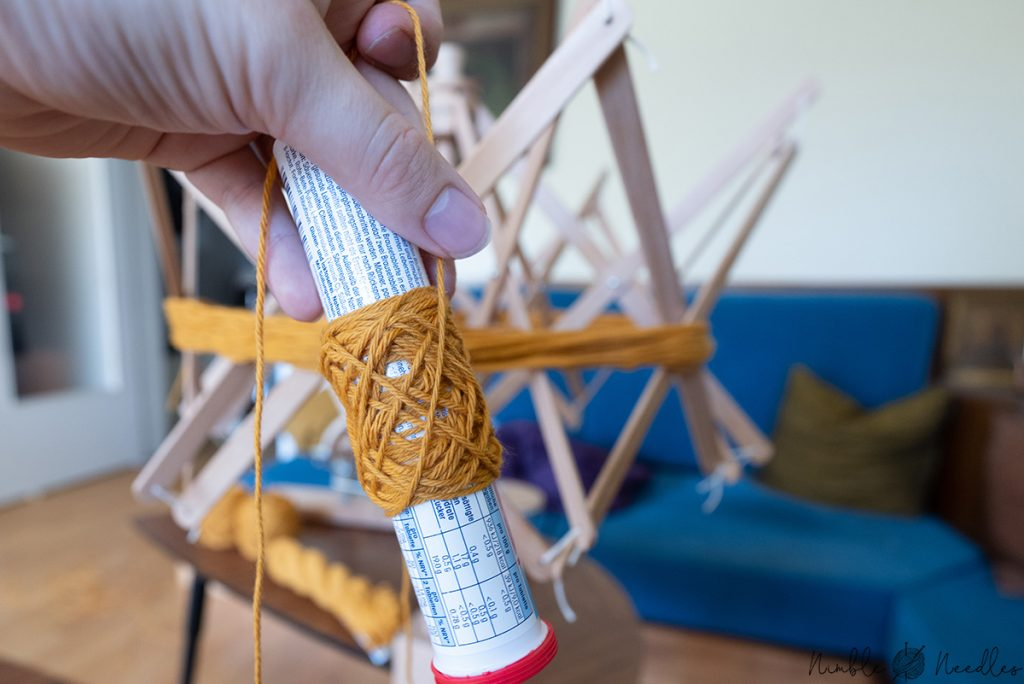 Manually wraping the yarn around a tube to create a yarn cake without a winderping