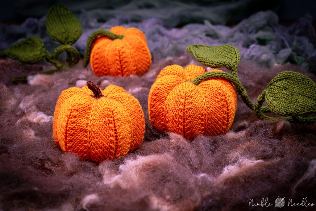 three knitted pumpkins with leaves in a patch
