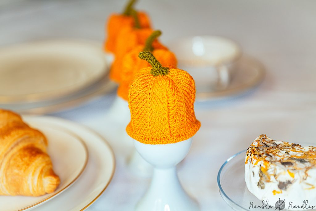 a row of pumpkin egg cozies on a breakfast table