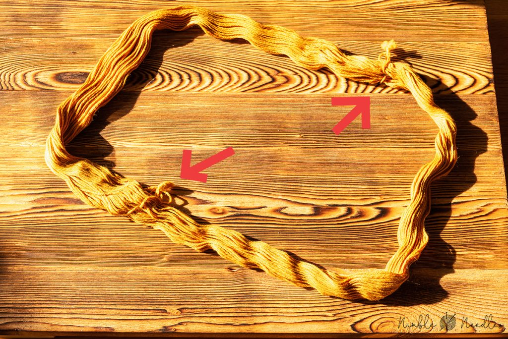 arrows marking the two positions where the hank is held together with knots