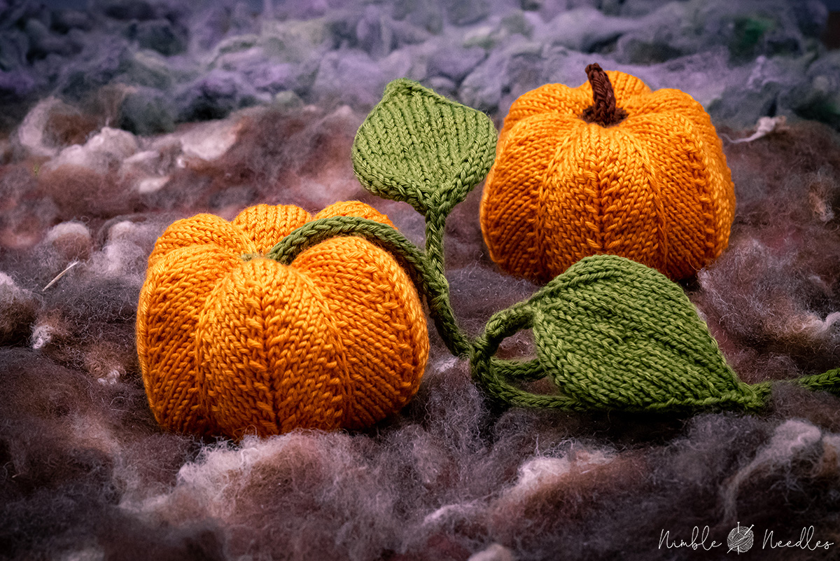 two knitted pumpkins with leaves in a little patch