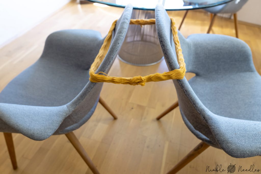 using the back of two chairs to unwind a hank of yarn without a swift