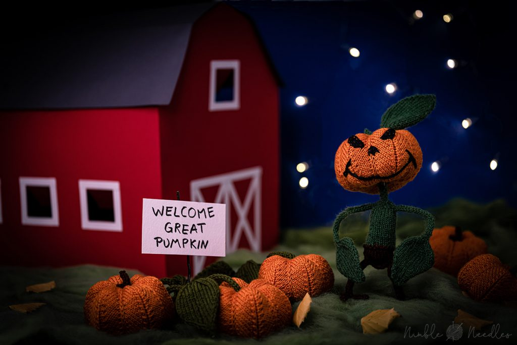 A knitted great pumpkin monster standing in a patch of pumpkins behind a red barn.