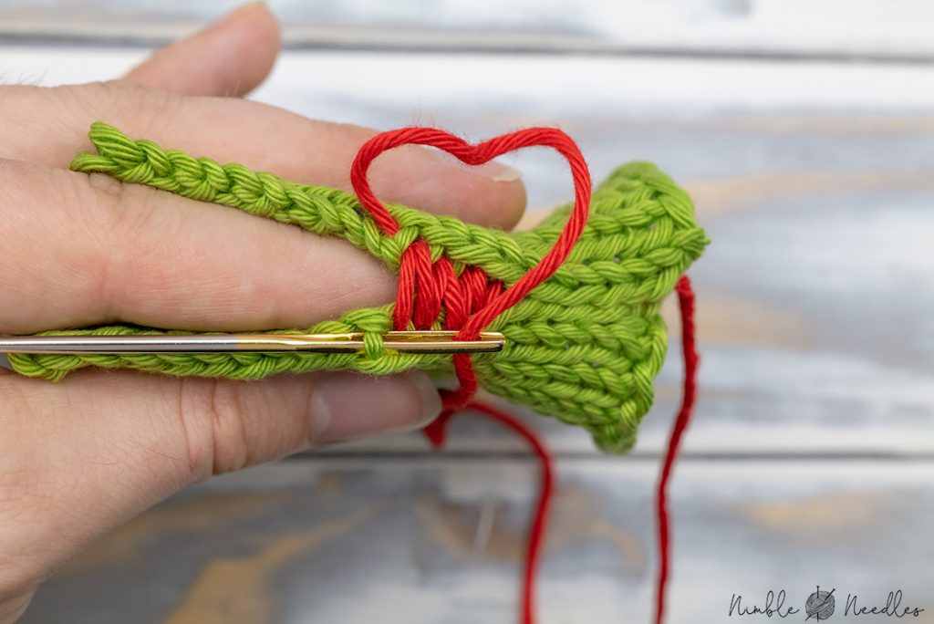 holding the seam between your thumb and index finger for easier stitching.