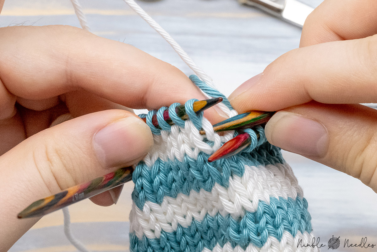 inserting the left needle into the right leg of the stitch one round below