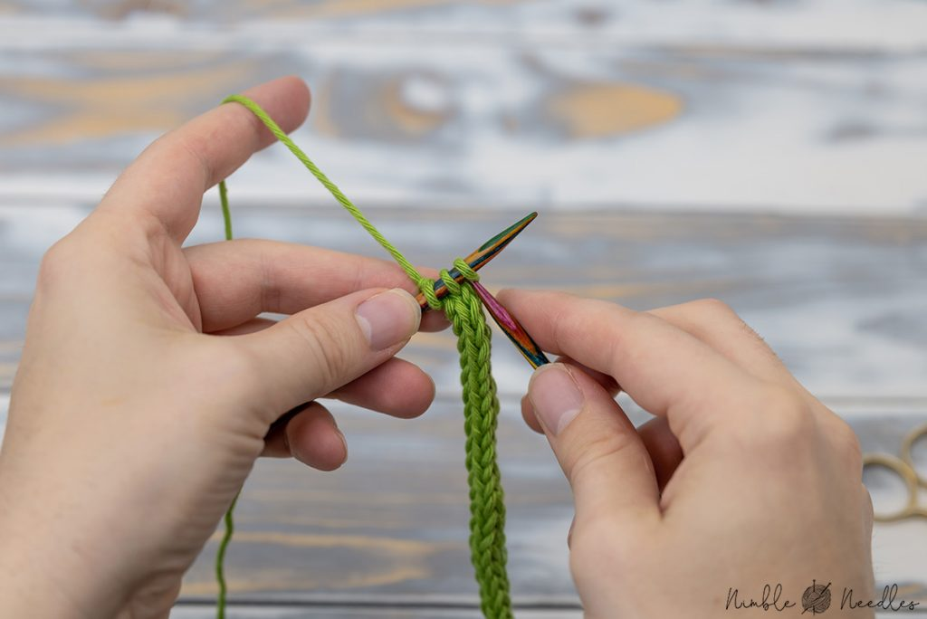 knitting an icord with 3 cast on stitches in green yarn