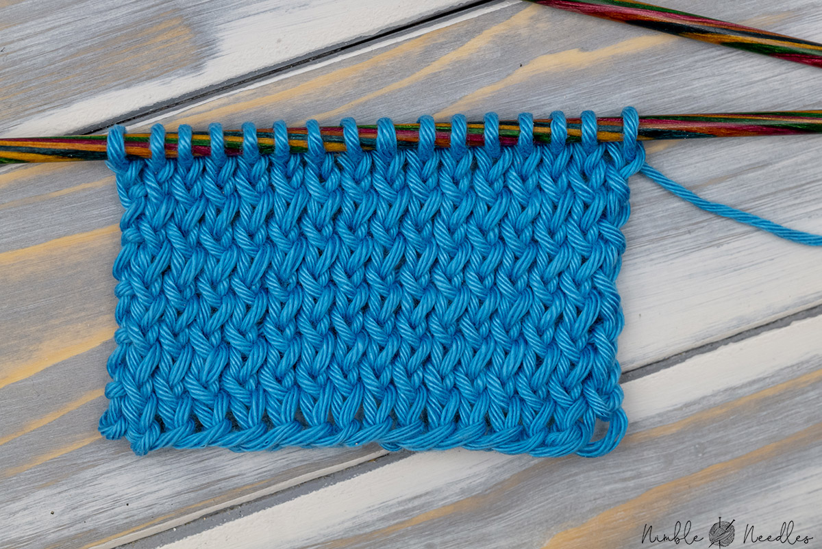 A swatch of stockinette stitch knitting with twisted stitches