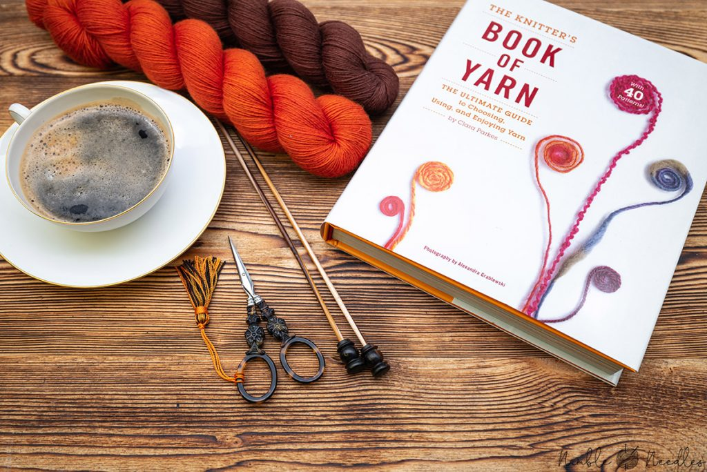 the knitter's book of yarn by clara parkes with some coffee and hanks of yarn