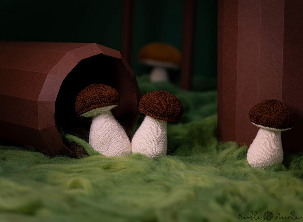 three different kinds of knitted mushrooms in a fake forest diorama - the perfect home decor