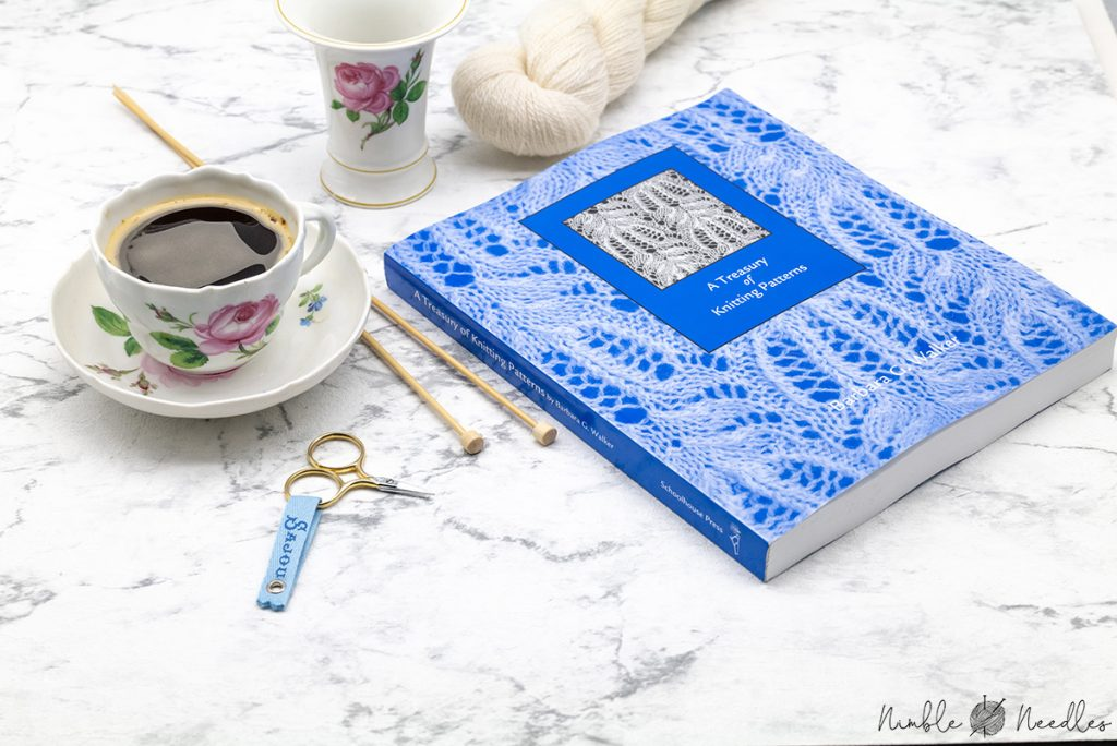a treasury of knitting patterns by barbara g walker with knitting needles and a cup of coffee