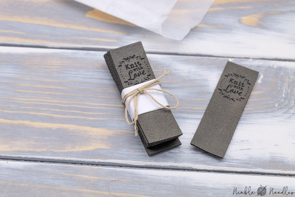 a couple of customized knitting tags on a wooden board