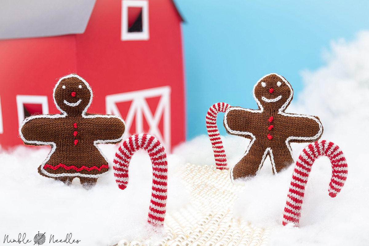 gingerbread man and woman christmas decoration in a fake landscape with sugar cane trees and a red barn
