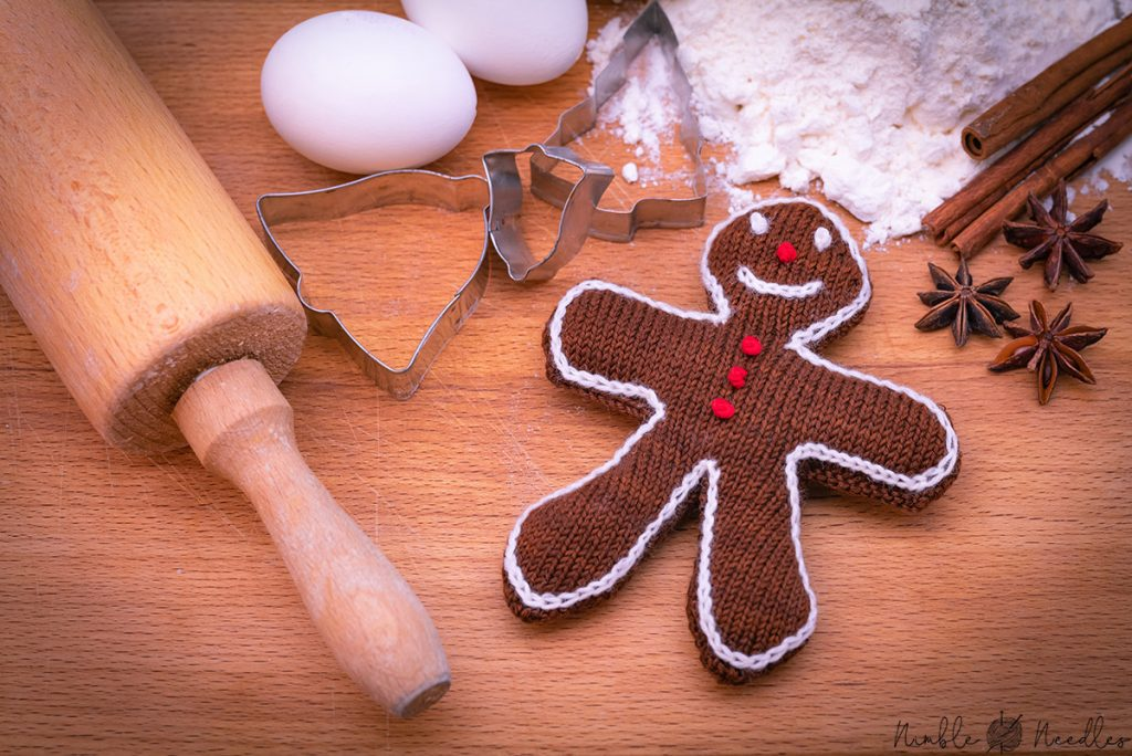 a knitted gingerbread christmas decoration with baking ingredients