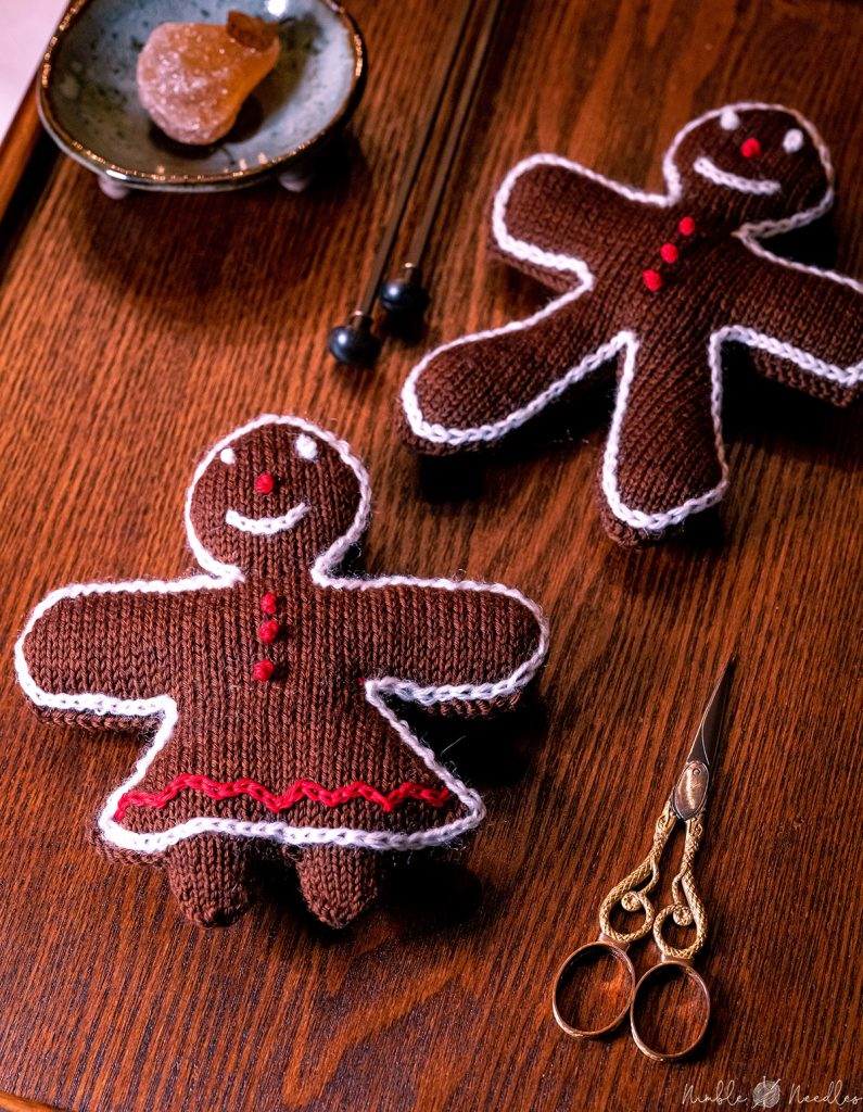 knitted gingerbread woman and man christmas decoration right after finishing the embroidery
