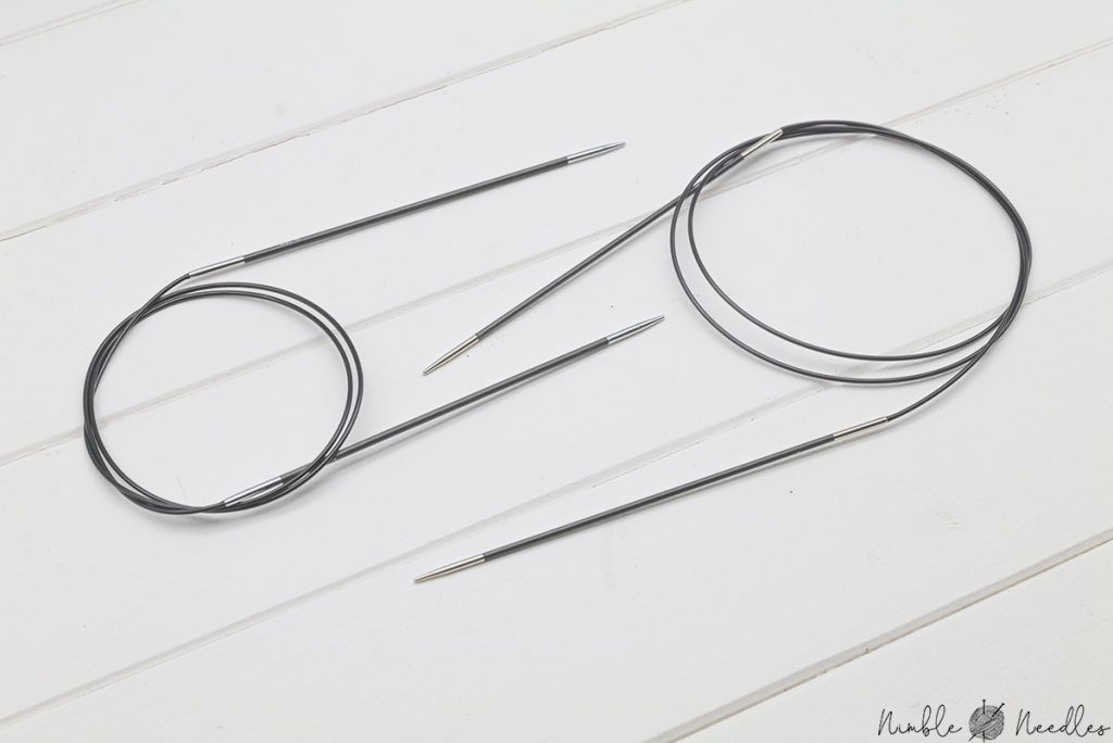 two pairs of knitter's pride fixed circular karbonz knitting needles next to each other