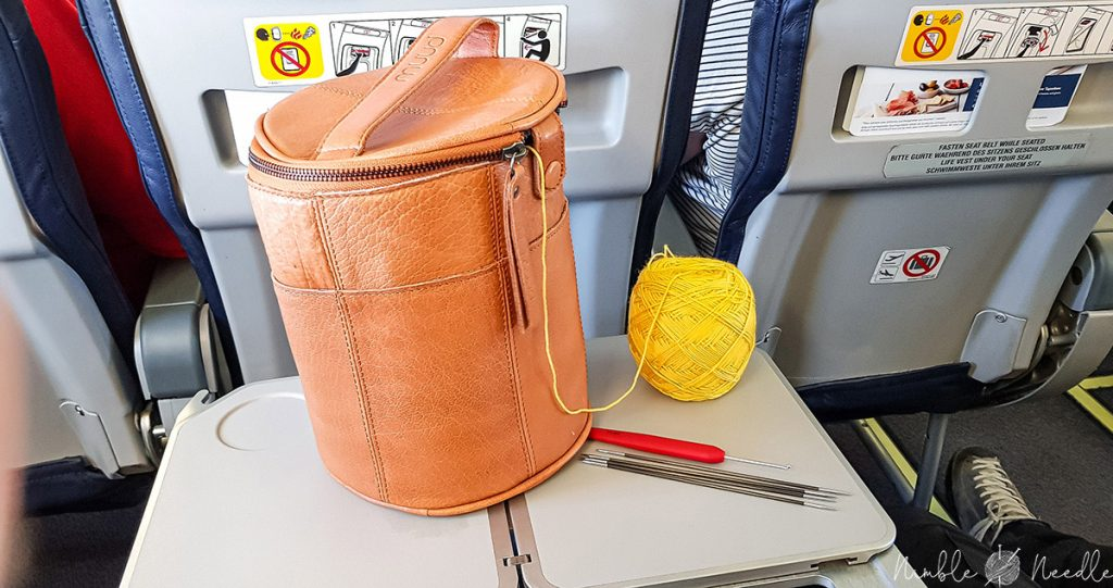double-pointed knitting needles on a plane with a crochet hook, yarn and a project bag