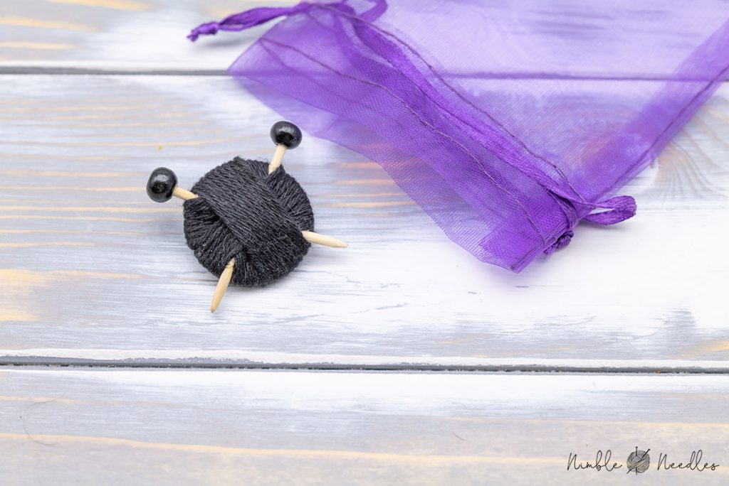 a black brooch in the shape of knitting needles sticking in a ball of yarn