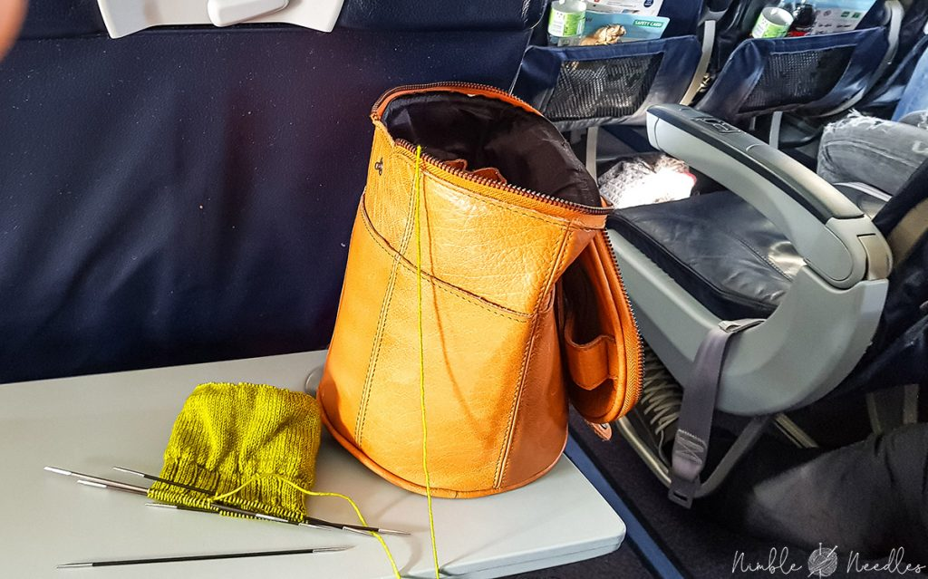 a knitting project and a nice leather bag with my knitting needles on a plane in europe
