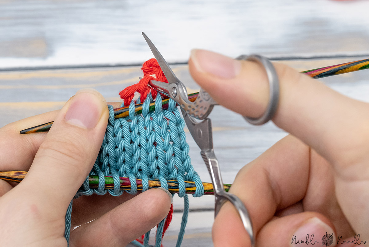 cutting a provisional cast-on open with a sissor because it didn't unravel by going in between the stitches